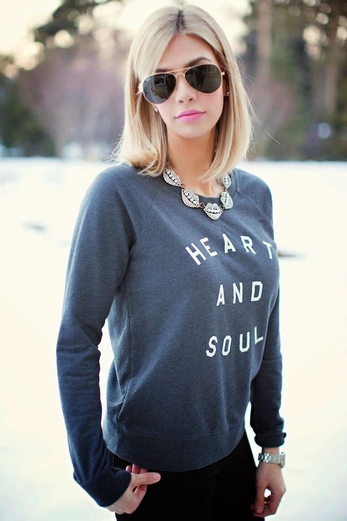 Lob Haarschnitt, blonde Haare, rosa Lippenstift und Sonnenbrille, grauer Sweatshirt mit weißer Aufschrift