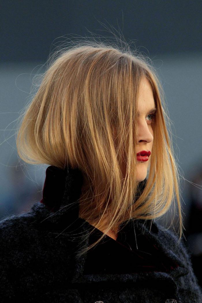 Dunkelblonde glatte Haare, Longbob Haarschnitt, roter Lippenstift, schwarzes Top und schwarzer Mantel