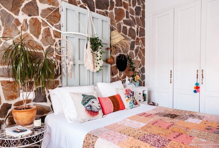 macrame dekoration in dem schlafzimmer, buntes ethno design, orientalisch dekorieren, steinwand, ein blumentopf mit pflanze am bett