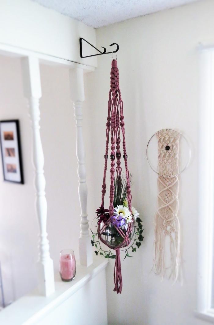 blumenampel makramee in farbe lila, ein runder blumentopf hängt in dem makrameedeko, weiße blumen