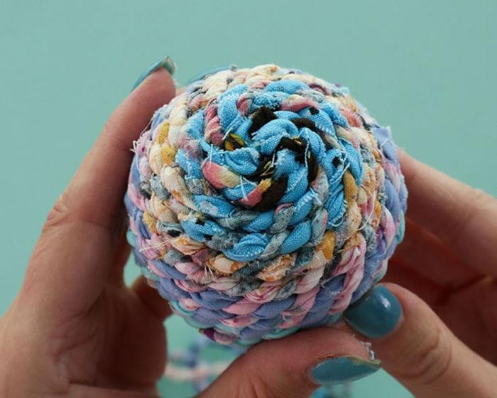 Garn in blauer und rosa Farbe, das fertige Endprodukt der Anleitung, Weihnachtskugeln selbst gestalten
