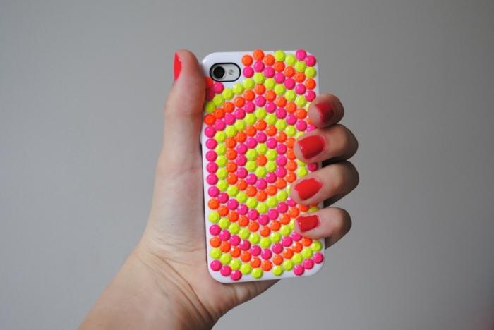 ein Hand trägt Handy mit Glasperlen bedeckt, Glasperlen in oranger, gelber und rosa Farbe, Handyhülle designen