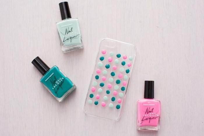 eine durchsichtige Handyhülle mit Nagellack verschönert, Tropfen von rosa und grüner Nagellack