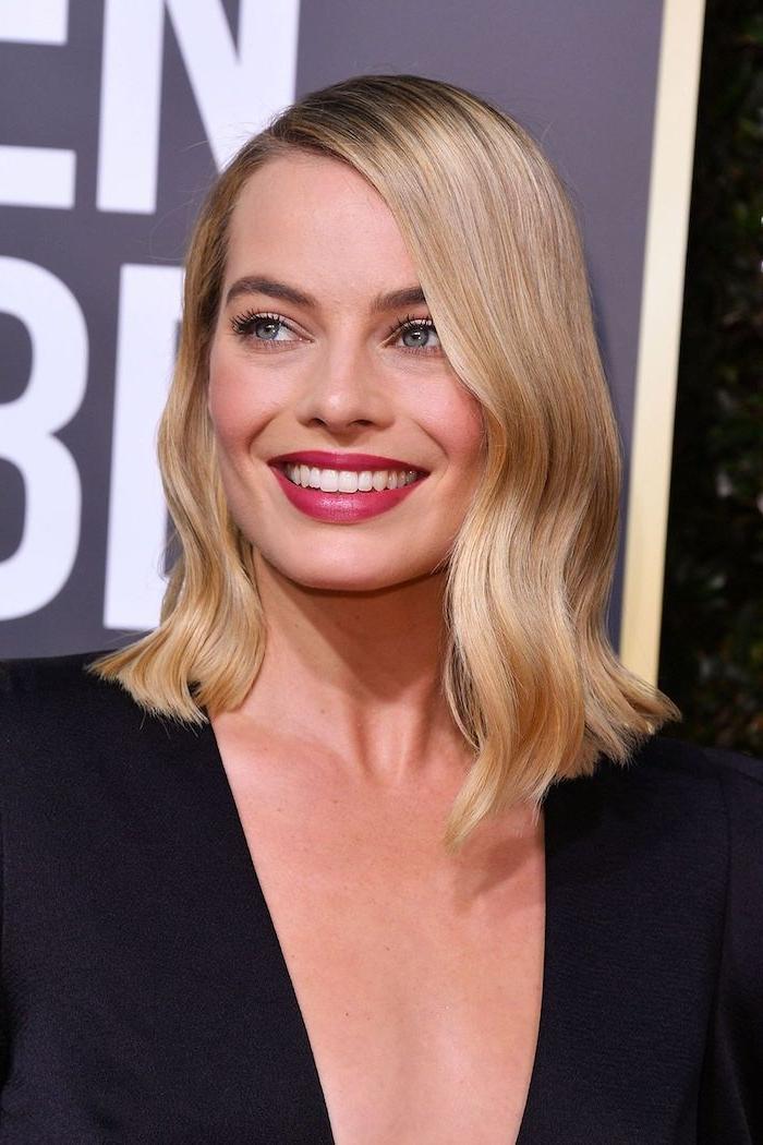 Blonde mittellange Haare mit Seitenscheitel, roter Lippenstift und schwarze Mascara, schwarzes Top mit V-Ausschnitt