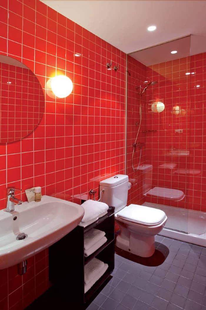 rotes badezimmer mit roten wänden und ein weißes waschbecken und kleiner spiegel und eine badezimmer lampe, badezimmer mit einer dusche