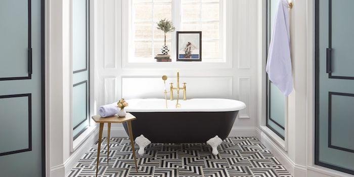 eine schwarze kleine freistehende badewanne und ein tisch aus holz, badezimmer mit weißen fenstern