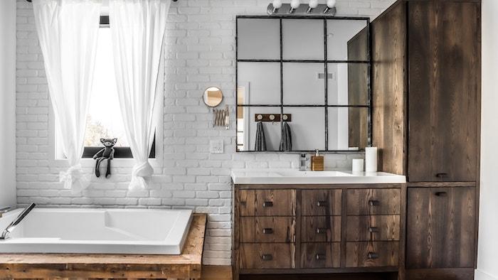 badezimmer mit fenster und einer weißen wand aus weißen steinen und weißen vorhängern, ein spiegel und badezimmer spiegelschrank