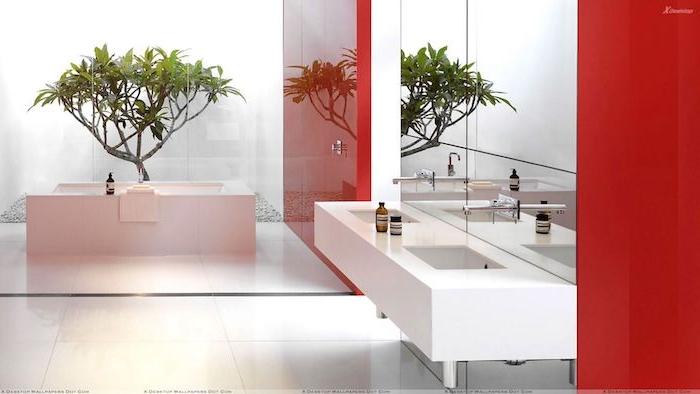 ein baum mit grünen blättern und eine kleine weiße freistehende badewanne, ein spiegel und weißes waschbecken, boden aus weißen fliesen
