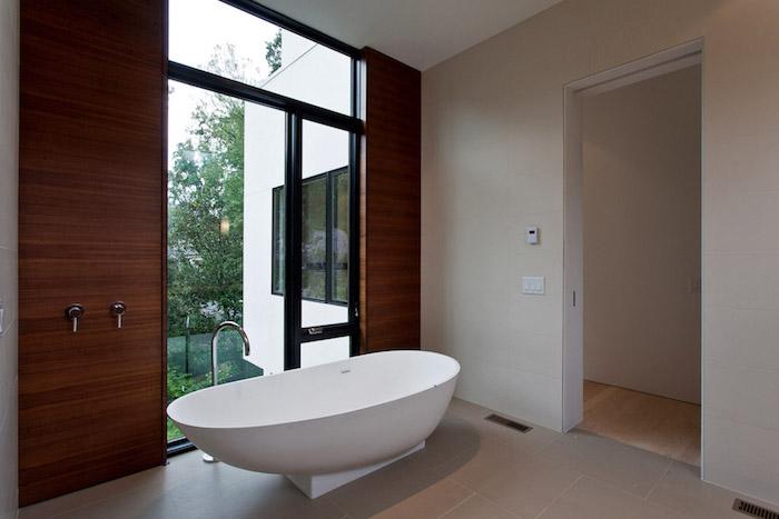garten und ein haus mit einem badezimmer mit fensern und einer großen weißen freistehenden badewanne, große badezimmer modern gestalten