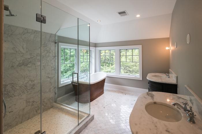 großes badezimmer mit einem weißen boden aus weißen badezimmer fliesen und mit großen weißen fenstern und freistehende badewanne
