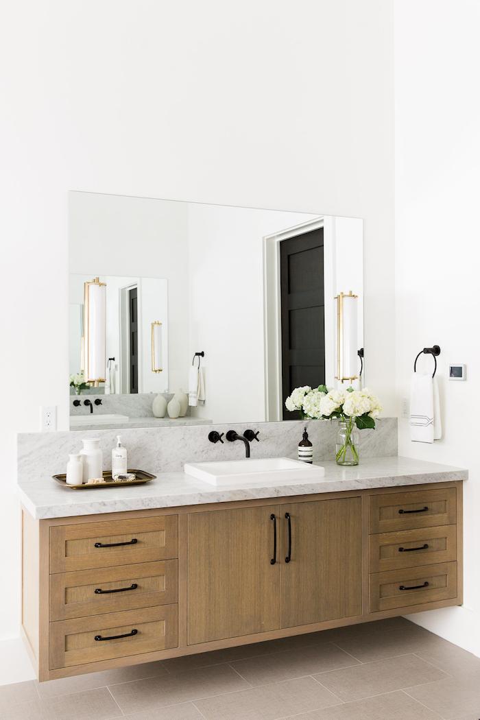 badezimer spiegelschrank aus holz und mit einem kleinen weißen waschbecken, zwei vasen mit weißen blumen
