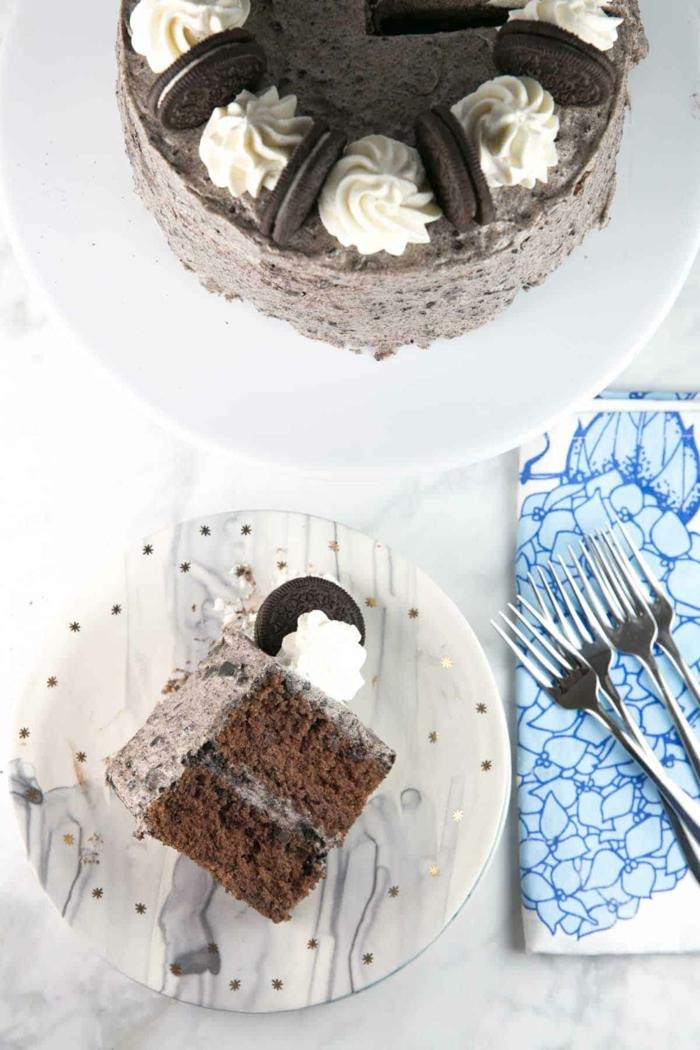 ein Stück Oreo Torte, zwei Schokoladenböden und Schokolade Creme dazwischen, weiße Dekoration
