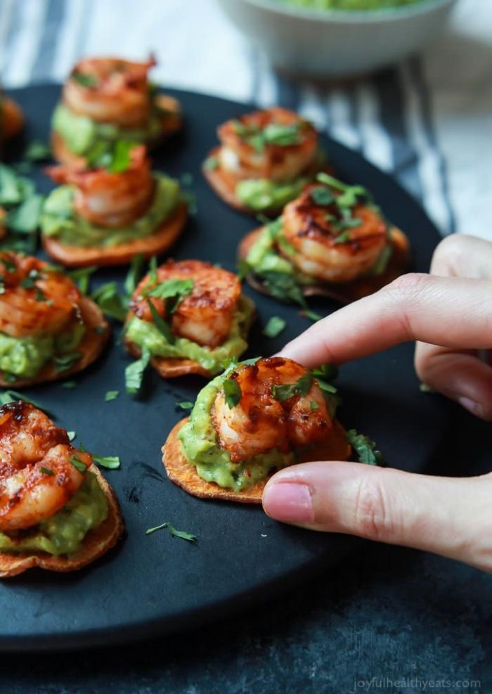 partyrezepte mit fleisch, runde schwarze servierplatte, gebratene garnelen, avocado