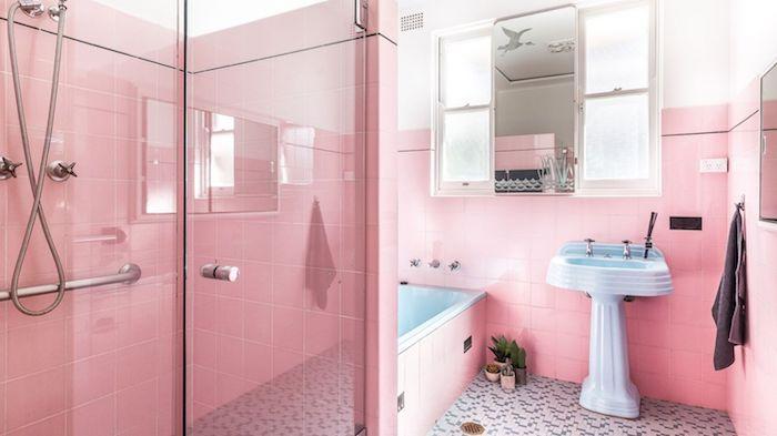 pinkes badezimmer mit pinken wänden mit vielen kleinen pinken badezimmer fliesen, ein blaues waschbecken und ein spiegel und eine dusche aus metall