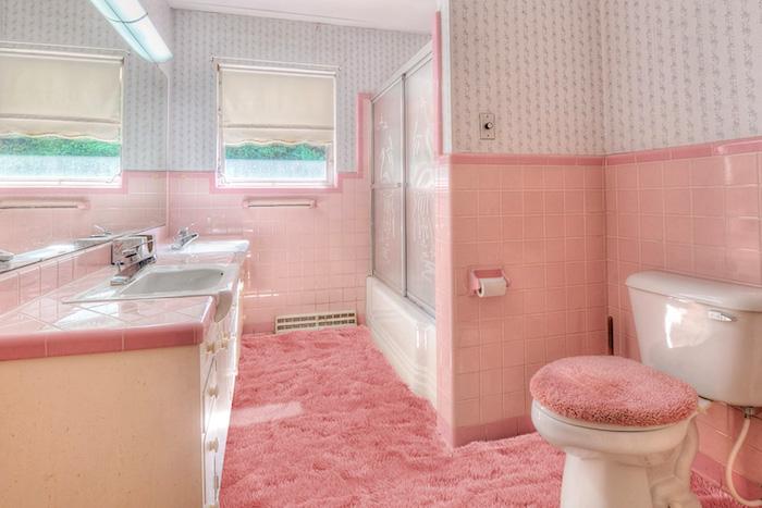 pinkes badezimmer mit einem pinken teppich und wänden mit pinken und weißen fliesen und ein pinkes waschbecken
