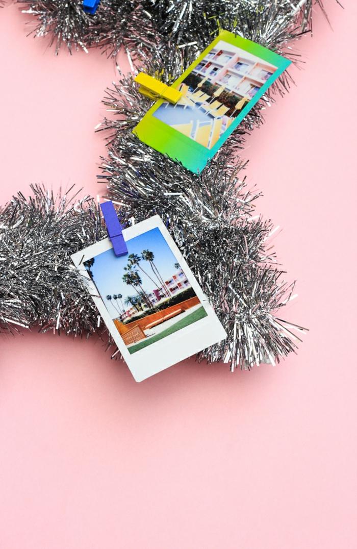 silberne Girlande mit vielen bunten Fotos auf Wäscheklammer gehängt, Sterne basteln