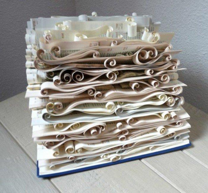 eine weiße Komposition, aus alten Büchern falten, viele Seiten wie Blüten, blauer Umschlag