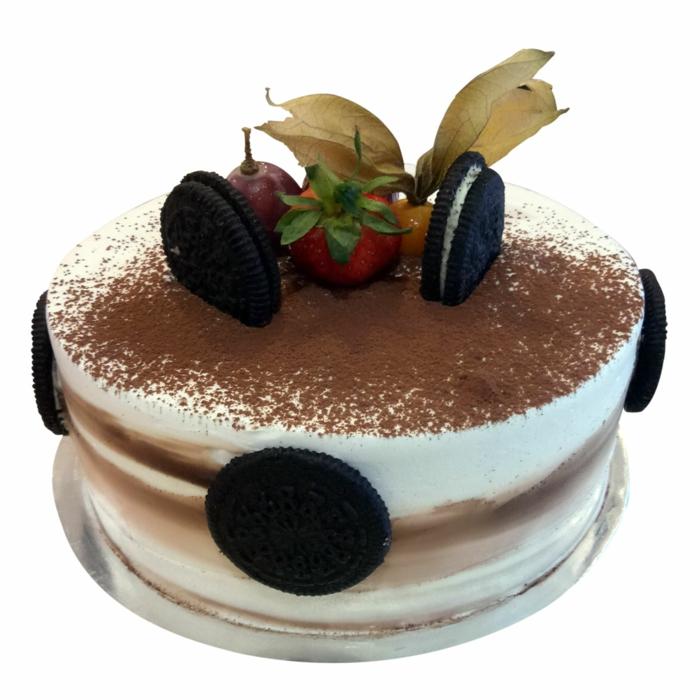 Torte mit Früchten, Torte mit weißer Creme, Erdbeeren und anderes Obst mit Zimt bestreut