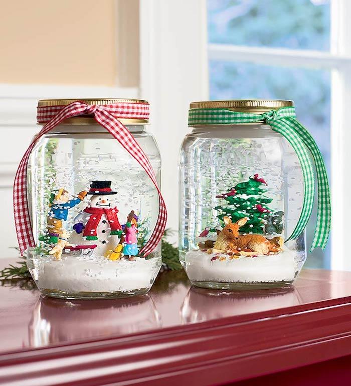 Zwei selbstgemachte Schneekugeln mit bunten Weihnachtsfiguren, Schneemann und Rentier, karierte Bänder um die Deckel