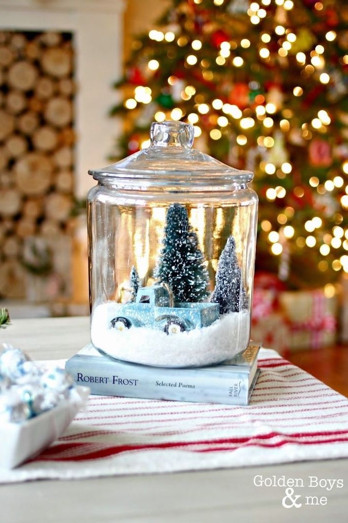 Große Schneekugel auf Buch, blaues Spielzeugauto und Weihnachtsbäume darin, mit künstlichem Schnee