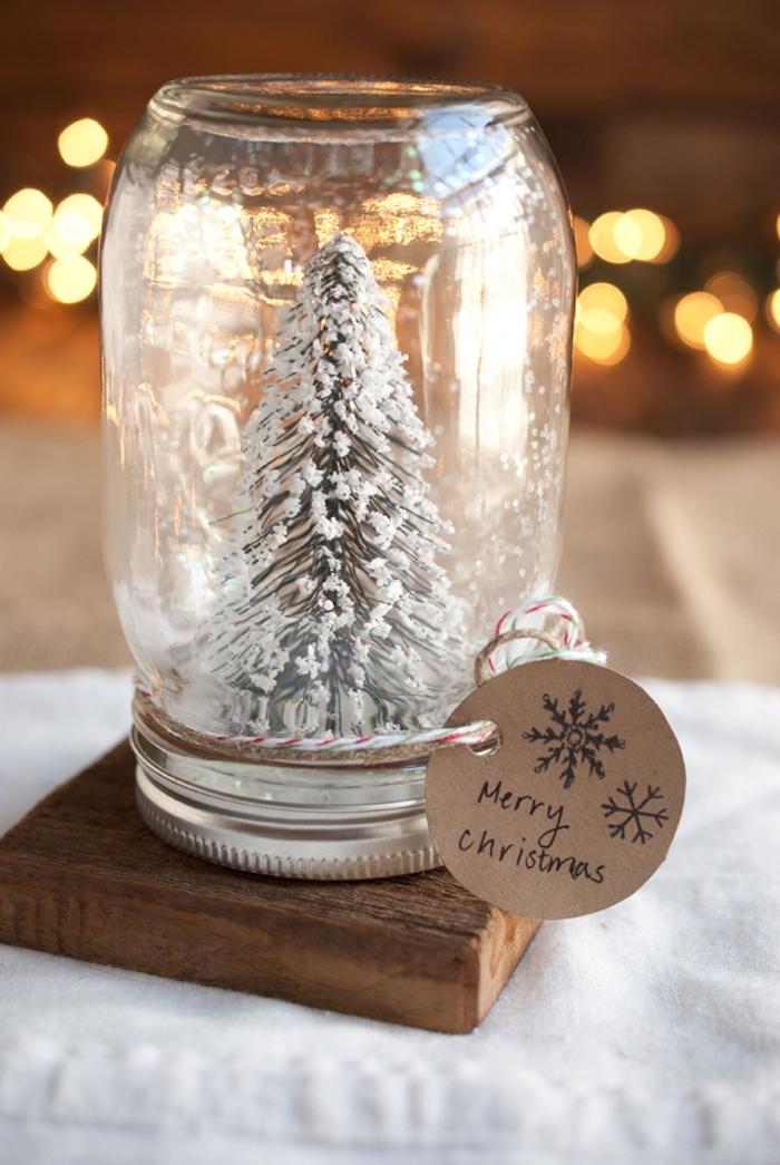 Schneekugel mit Weihnachtsbaum, Faden um den Deckel, kleine Grußkarte mit Aufschrift Frohe Weihnachten