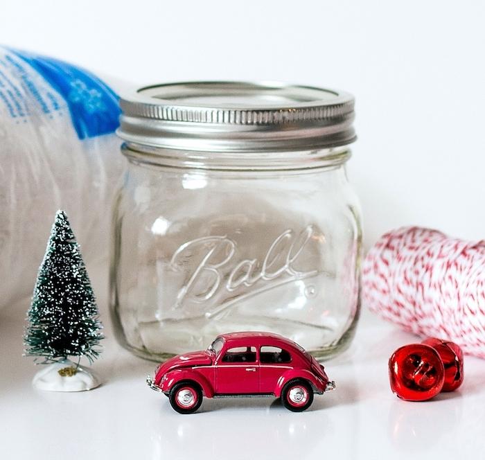 Schneekugel selber machen, Spielzeugauto und Weihnachtsbaum darin stecken, Faden und Glöckchen für den Deckel