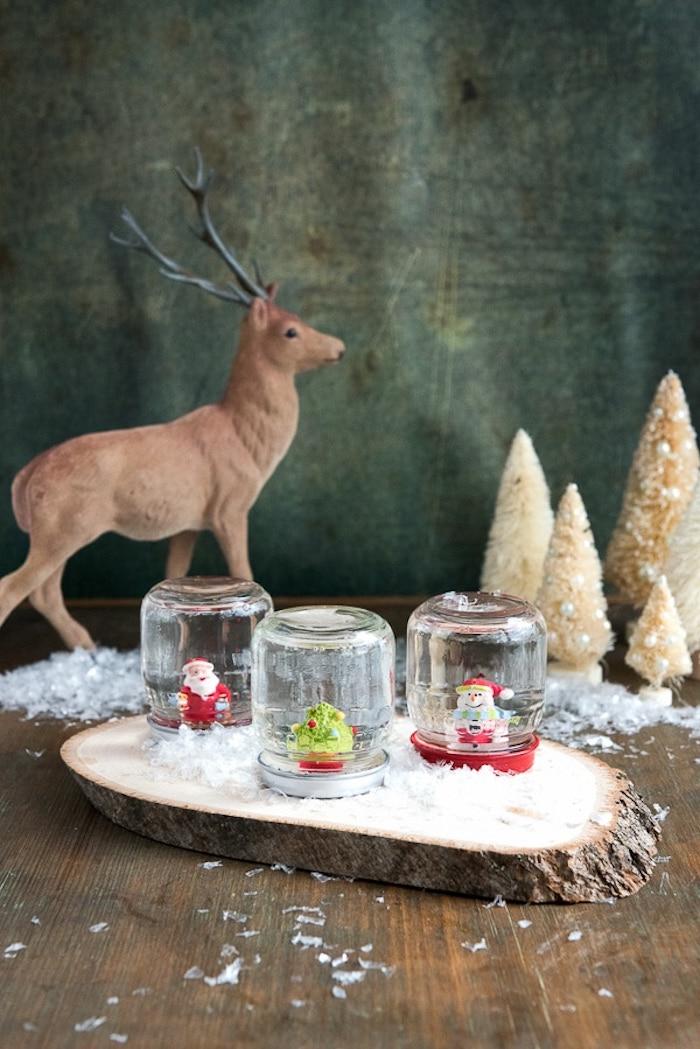 Drei selbstgemachte Schneekugeln mit Weihnachtsmann, Christbaum und Schneemann