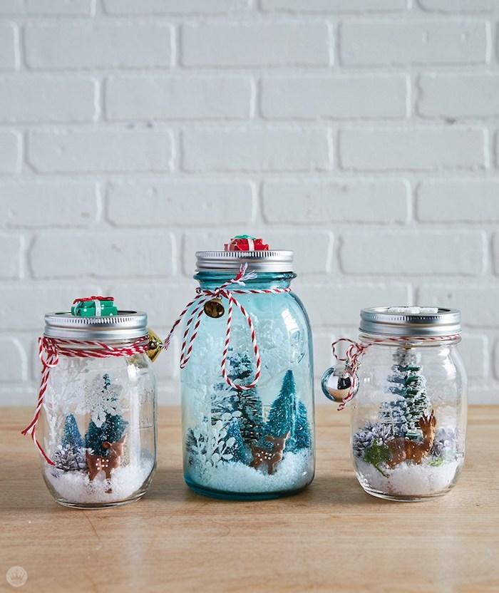 Drei selbstgemachte Schneekugeln mit Rentieren und Weihnachtsbäumen darin, dekoriert mit Faden und kleinen Glöckchen