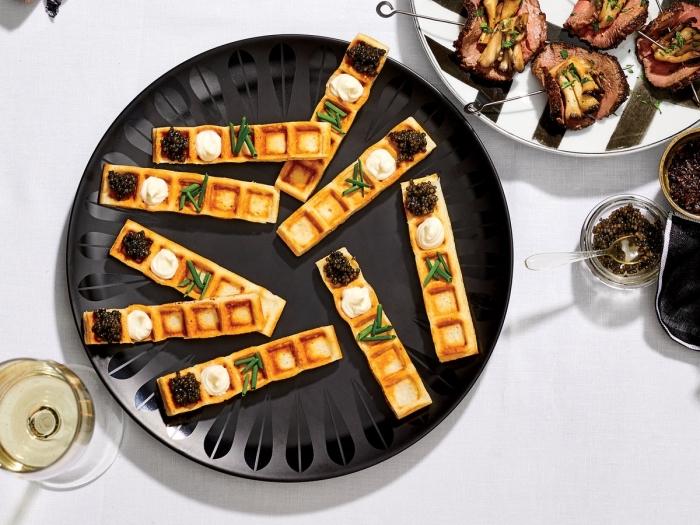 waffeln mit caviar und creme, schnelle partysnacks, runder schwarzer teller, weißwein