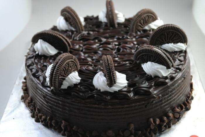 eine Torte mit Schokoladenglasur. weiße Sahne und halbe Oreos, Oreo selber machen, Schokoladennüssen
