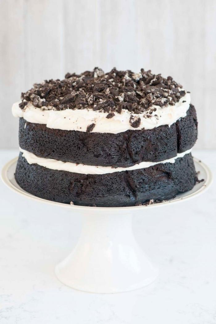 zwei Schokoladenböden mit Milchcreme in der Mitte und oben, Oreo Krümmel als Dekoration, Oreo Rezept