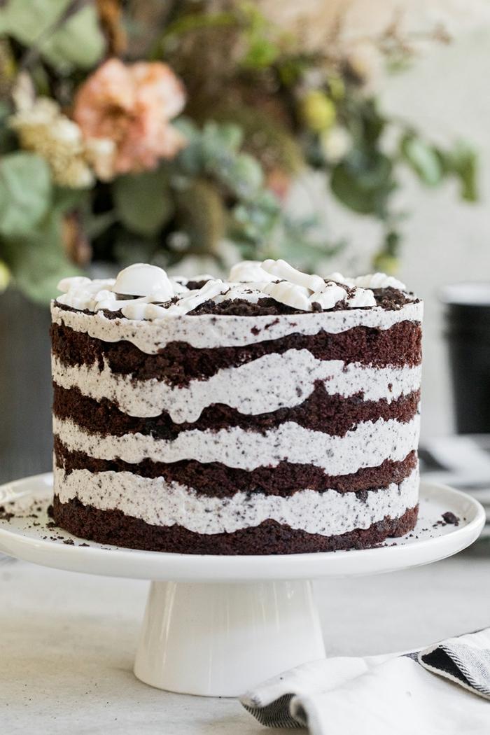 vier Schokoladenböden, weiße Creme dazwischen, Oreo Kuchen Rezept, rosa Rosen im Hintergrund