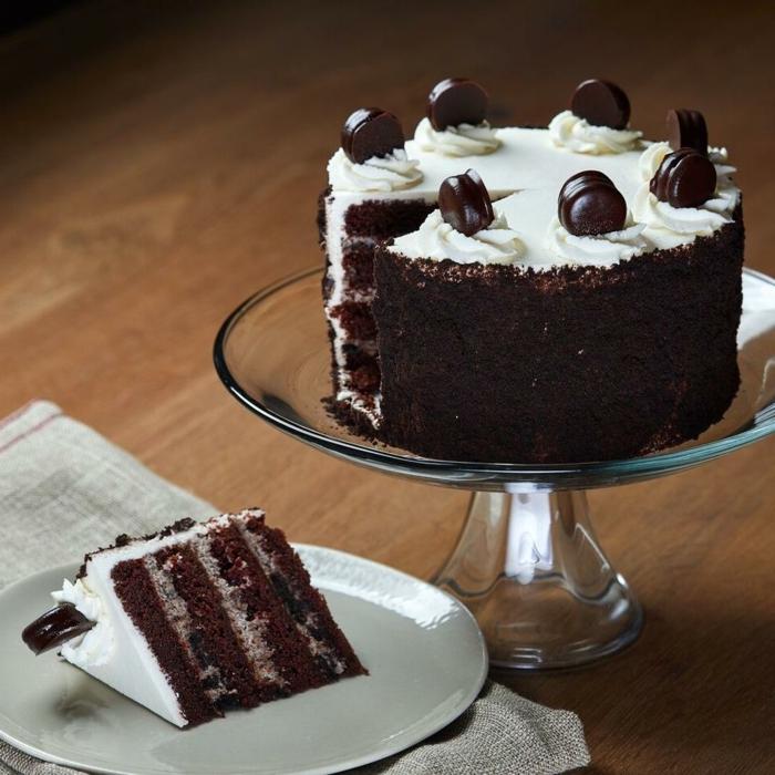 vier Schokoladenböden, mit weißer Creme bedeckt, mit Oreo Creme befüllt, mit Pralinen verziert