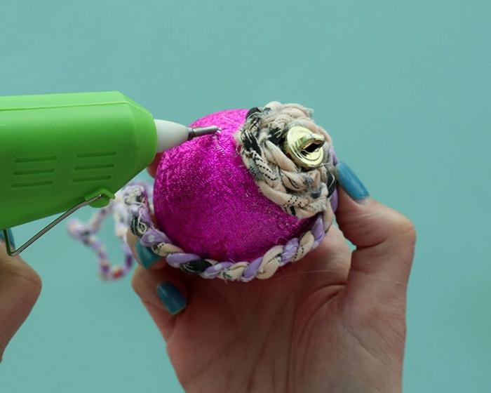 eine lila Kugel durch Heißkleberpistole mit Klebstoff bedecken, Weihnachtskugeln selbst gestalten