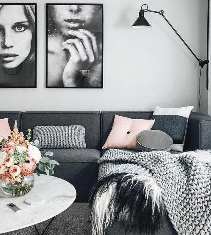ein graues Sofa, rosa Kissen, weiße Wandfarbe, ein weißer runder Couchtisch, Wohnzimmer Weiß Grau