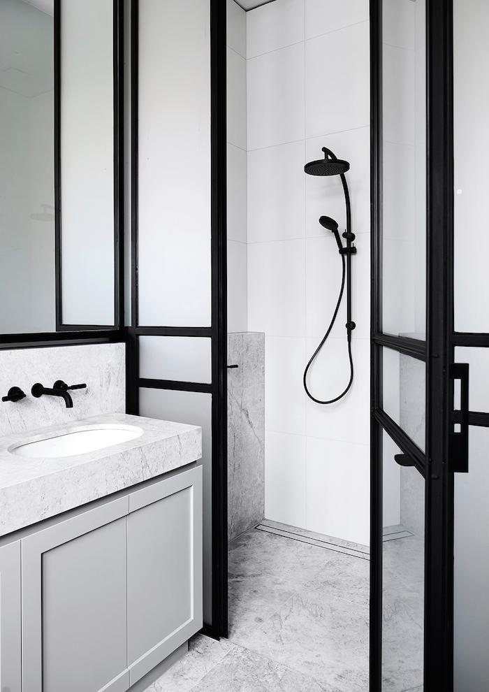 ein badezimmer mit weißen und schwarzen wänden und ein weißes waschbecken und eine schwarze dusche aus metall