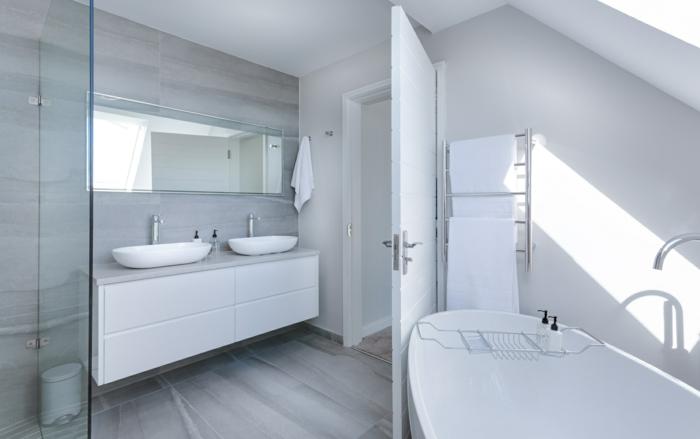 ein weißes Badezimmer mit großer Spiegel