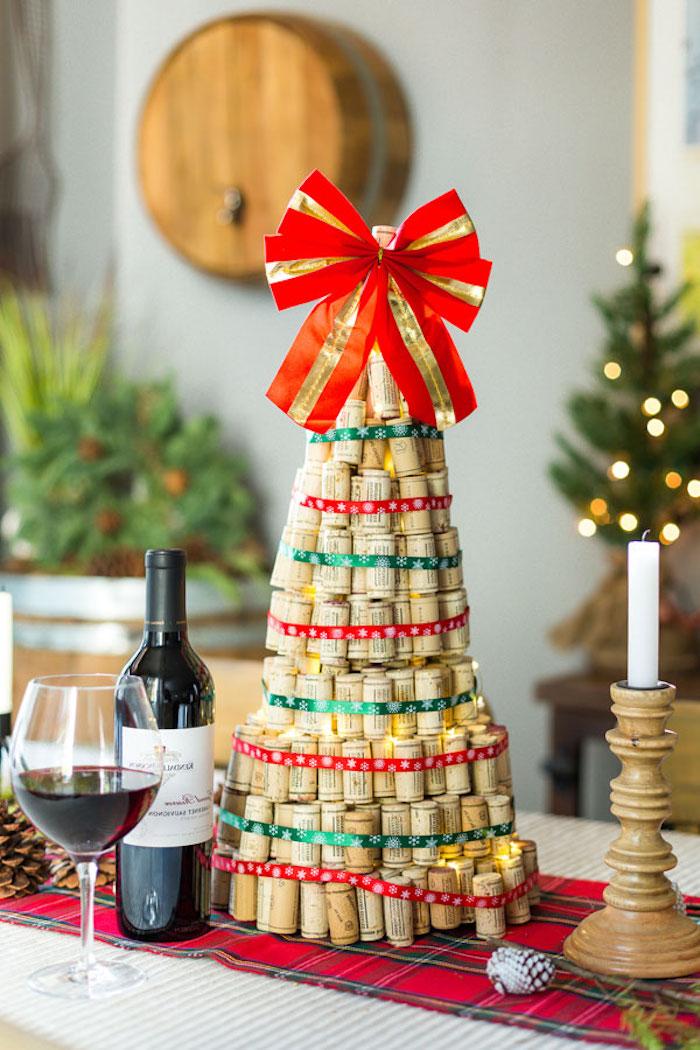 Selbstgemachter Weihnachtsbaum aus Weinkorken, geschmückt mit großer roter Schleife, Weinflasche und Weinglas