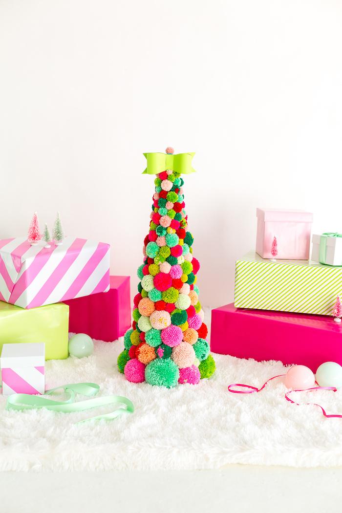 Kleiner Weihnachtsbaum aus bunten selbstgemachten Pompons, grüne Schleife an der Spitze