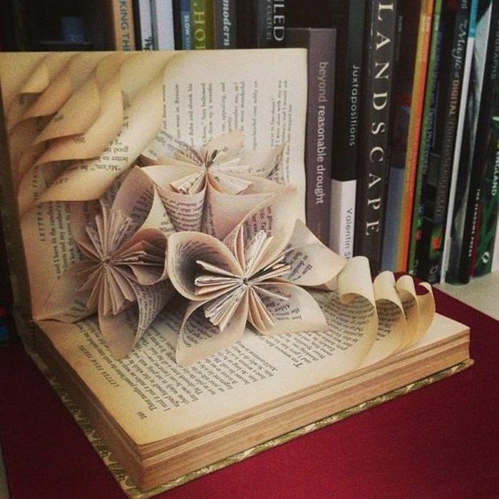gefaltete Bücher, ein Buch auf dem Bücherregal mit vielen kleinen Papierblütten als Dekoration