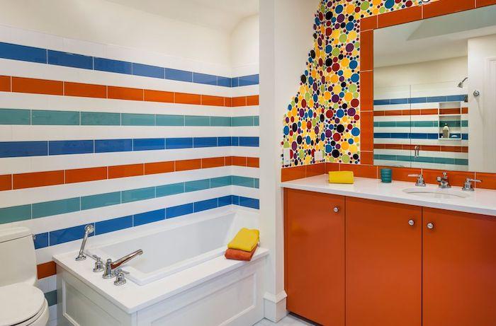 kleine weiße badewanne mit wänden aus bunten fliesen, ein oranger badezimmer spiegelschrank, badezimmer modern