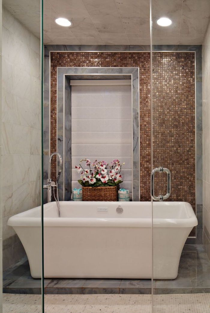 blumentopf mit pinken und violetten blumen mit grünen blättern, eine weiße freistehende badewanne im badezimmer mit braunen und grauen badezimmer fliesen