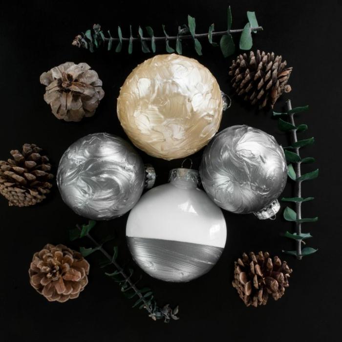 einige Weihnachtsdekorationen nebeneinander, goldene Kugel von silbernen Kugeln umgeben, Weihnachtskugeln basteln
