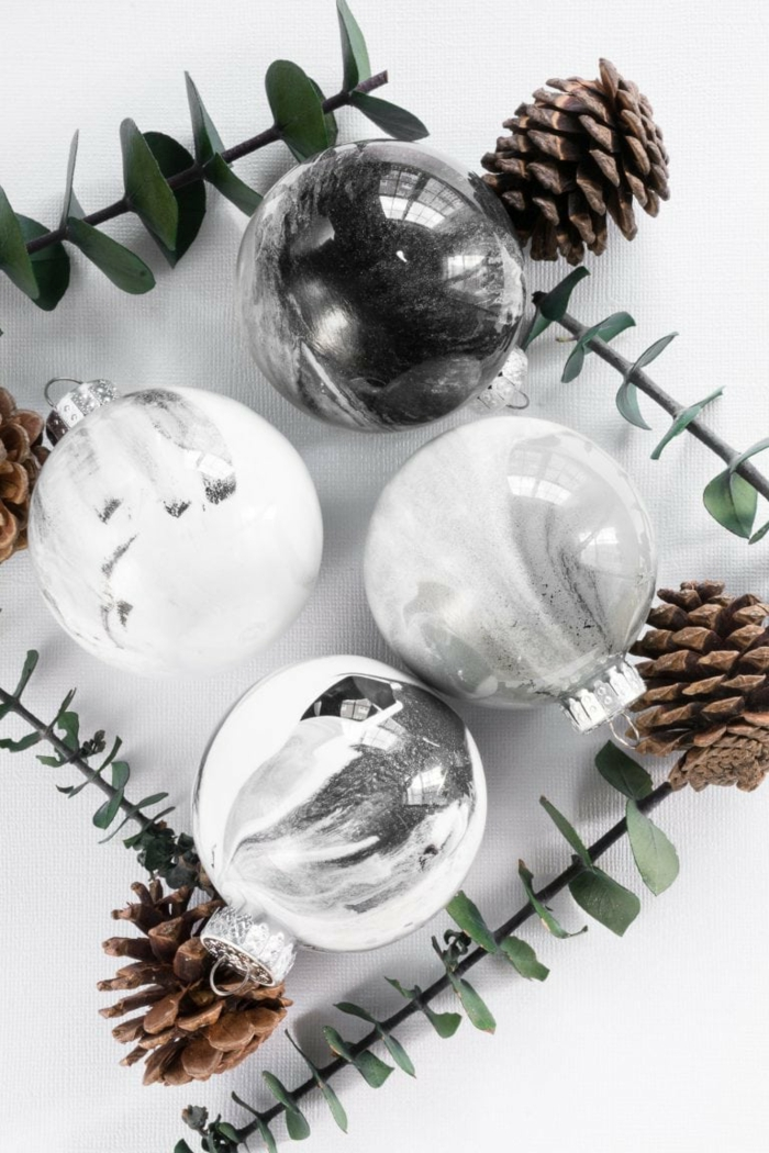 vier Kugeln in weißer und grauer Farbe, Zapfen und kleine Zweige, Christmasbaumskugeln