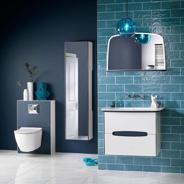 blaue wand aus blauen badezimmer fliesen und ein spiegel, blaue badezimmer lampe und weiße vasen mit grünen pflanzen