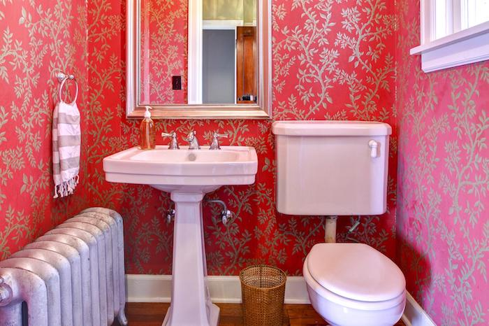 weißes waschbecken und ein spiegel im badezimmer mit roten wänden und einem weißen fenster