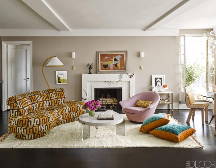 wanddeko wohnzimmer, deigner sessel in rosa, große kissen, weißer teppich, kamin
