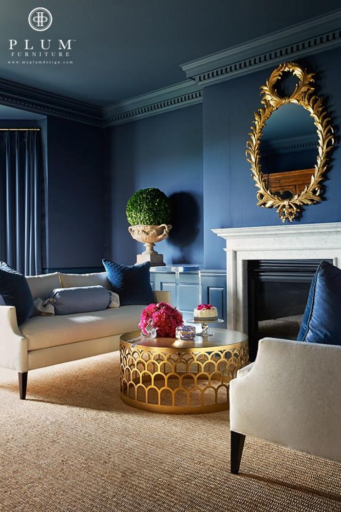 wanddeko wohnzimmer, dunkelblaue wandfarbe, spiegle mit golddenem rahmen, kaffeetisch mit metallenen akzenten