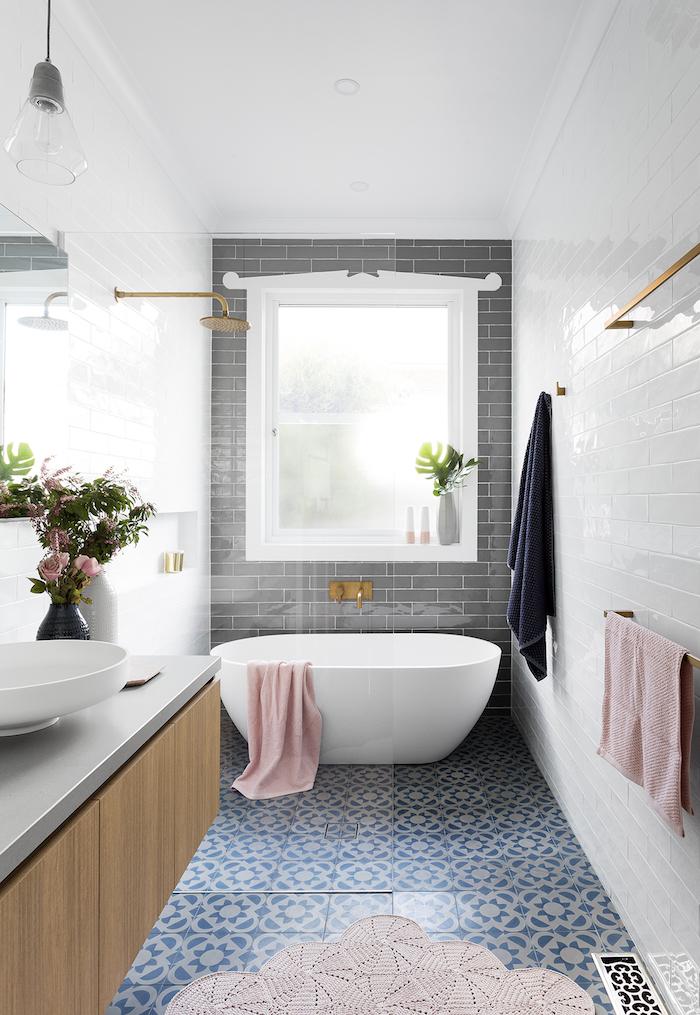 boden aus vielen blauen badezimmer fliesen, ein badezimmer mit einer weißen freistehenden badewanne und pinken tüchern, eine vase mit pinken blumen, badezimmer mit fenster