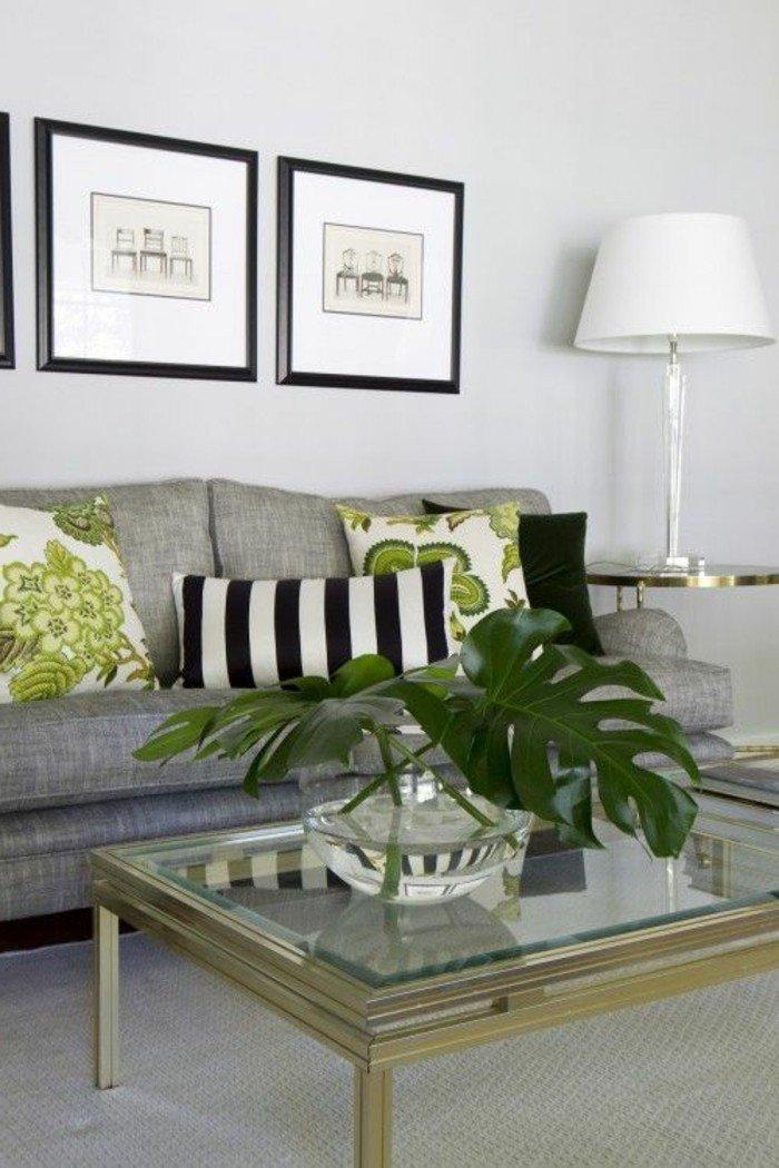 ein graues Sofa, grüne Kissen, Tisch aus Glas, eine Vase mit großen Blättern, Wohnzimmer Weiß Grau